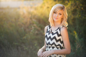 senior in chevron dress looking into the camera with beautiful golden sunlight