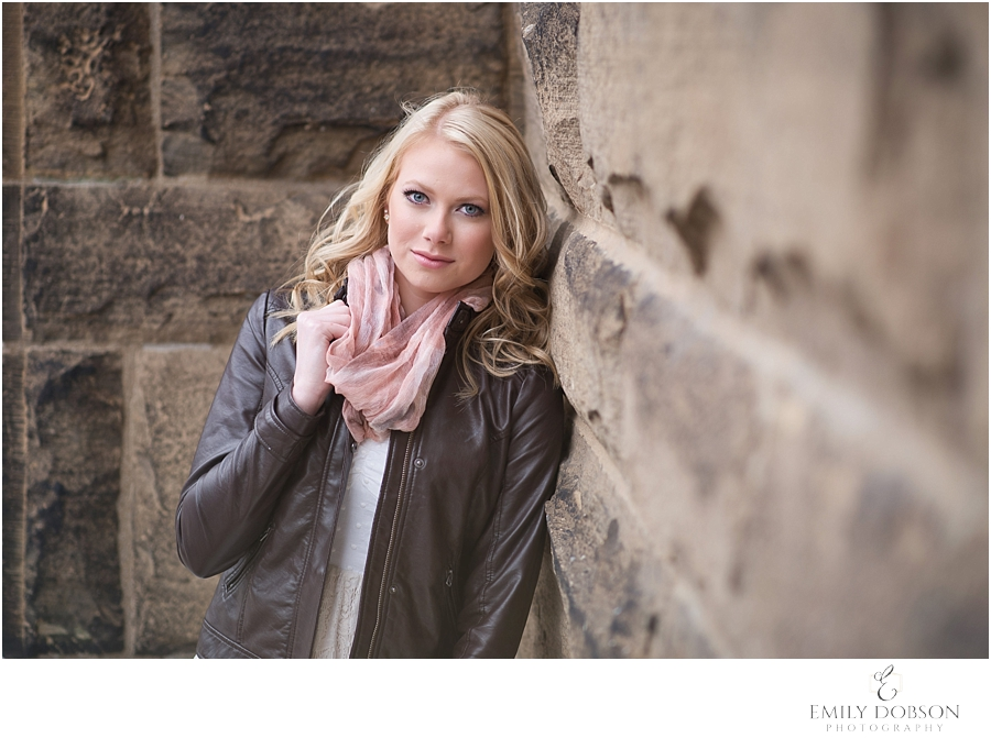 blonde HS senior leaning against a stone building in a leather jacket and scarf